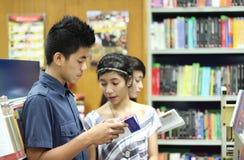 Allievi nella libreria Immagine Stock