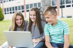 allievi Pre-teenager della scuola fuori dell'aula con il computer portatile Immagine Stock