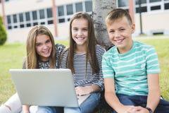 allievi Pre-teenager della scuola fuori dell'aula con il computer portatile Fotografia Stock Libera da Diritti