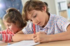 Allievi a scrittura della scuola in taccuini Fotografia Stock