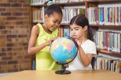 Allievi sorpresi che studiano globo nella biblioteca Fotografie Stock