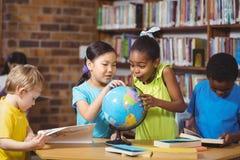 Allievi sorpresi che studiano globo nella biblioteca Fotografia Stock Libera da Diritti