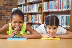 Allievi sorridenti che si appoggiano i libri nella biblioteca Fotografie Stock