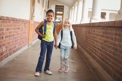 Allievi sorridenti che si tengono per mano al corridoio Fotografia Stock