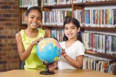 Allievi sorridenti che studiano globo nella biblioteca Fotografia Stock
