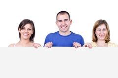 Allievi sorridenti che tengono un tabellone per le affissioni Immagini Stock Libere da Diritti