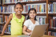 Allievi sorridenti che utilizzano computer portatile nella biblioteca Fotografia Stock