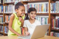 Allievi sorridenti che utilizzano computer portatile nella biblioteca Fotografia Stock Libera da Diritti