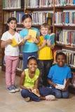 Allievi sorridenti con i libri nella biblioteca Fotografia Stock