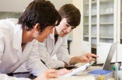 Allievi sorridenti di chimica che scrivono un rapporto Immagini Stock