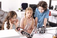 Allievi stupiti che collaudano i robot elettronici alla scuola Fotografie Stock Libere da Diritti