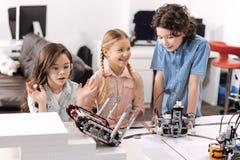 Allievi stupiti che collaudano i robot elettronici alla scuola Fotografia Stock Libera da Diritti