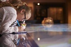 Allievi sul viaggio al museo che esamina mappa e che fa le note Immagini Stock