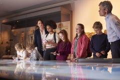 Allievi sul viaggio al museo che esamina mappa e che fa le note Immagine Stock