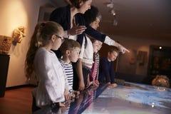 Allievi sull'escursione della scuola al museo che esamina mappa Fotografia Stock