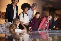 Allievi sull'escursione della scuola al museo che esamina mappa Fotografie Stock Libere da Diritti