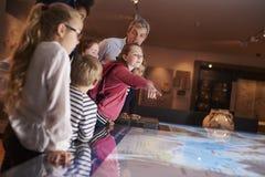 Allievi sull'escursione della scuola al museo che esamina mappa Immagini Stock