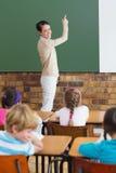 Allievi svegli che ascoltano il loro insegnante in aula Fotografie Stock Libere da Diritti