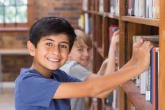Allievi svegli che cercano i libri in biblioteca Fotografie Stock Libere da Diritti