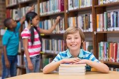 Allievi svegli che cercano i libri in labrary Fotografia Stock