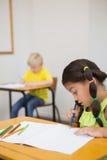 Allievi svegli che colorano agli scrittori in aula Immagini Stock
