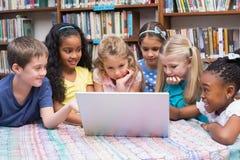 Allievi svegli che esaminano computer portatile in biblioteca Fotografia Stock