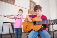 Allievi svegli che giocano flauto e chitarra in aula Fotografia Stock