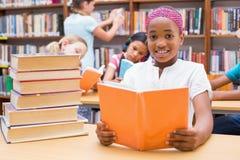 Allievi svegli che leggono nella biblioteca Immagini Stock