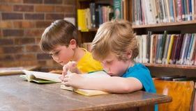 Allievi svegli che leggono nella biblioteca Fotografia Stock