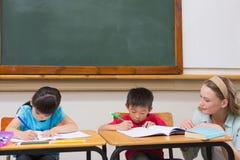 Allievi svegli che ottengono aiuto dall'insegnante in aula Fotografia Stock
