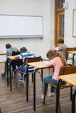 Allievi svegli che scrivono agli scrittori nell'aula Immagini Stock