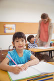 Allievi svegli che scrivono allo scrittorio nell'aula Immagini Stock