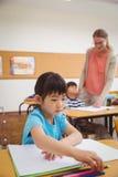 Allievi svegli che scrivono allo scrittorio nell'aula Fotografie Stock Libere da Diritti