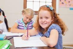 Allievi svegli che scrivono allo scrittorio nell'aula Fotografia Stock