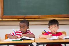 Allievi svegli che scrivono allo scrittorio nell'aula Immagine Stock