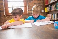 Allievi svegli che scrivono nella biblioteca Immagini Stock Libere da Diritti