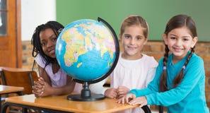 Allievi svegli che si siedono nell'aula con il globo Fotografie Stock