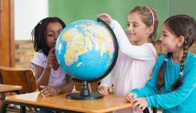 Allievi svegli che si siedono nell'aula con il globo Immagini Stock Libere da Diritti