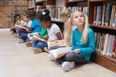 Allievi svegli che si siedono sul pavimento in biblioteca Immagine Stock Libera da Diritti