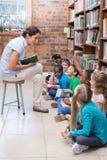 Allievi svegli che si siedono sul pavimento in biblioteca Fotografie Stock Libere da Diritti