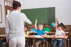 Allievi svegli che sollevano le loro mani nella classe Immagini Stock