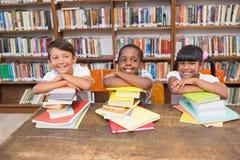 Allievi svegli che sorridono alla macchina fotografica alla biblioteca Immagine Stock