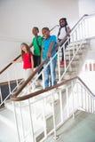Allievi svegli che sorridono alla macchina fotografica che cammina giù le scale Immagini Stock Libere da Diritti