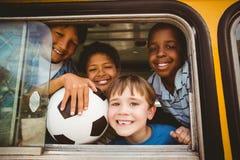 Allievi svegli che sorridono alla macchina fotografica nello scuolabus Fotografia Stock Libera da Diritti