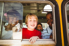 Allievi svegli che sorridono alla macchina fotografica nello scuolabus Immagine Stock