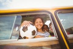 Allievi svegli che sorridono alla macchina fotografica nello scuolabus Fotografie Stock Libere da Diritti