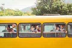 Allievi svegli che sorridono alla macchina fotografica nello scuolabus Immagini Stock