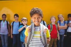 Allievi svegli che sorridono alla macchina fotografica in scuolabus Fotografia Stock