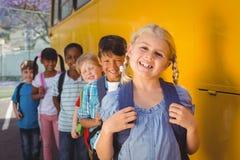 Allievi svegli che sorridono alla macchina fotografica in scuolabus Fotografie Stock Libere da Diritti