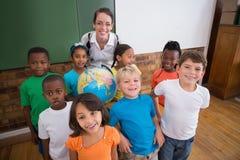 Allievi svegli che sorridono intorno ad un globo in aula con l'insegnante Immagini Stock Libere da Diritti